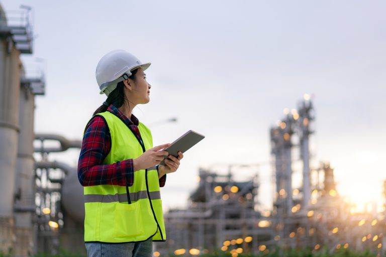 Asian woman petrochemical engineer working with digital tablet Inside oil and gas refinery plant industry factory for inspector safety quality control..